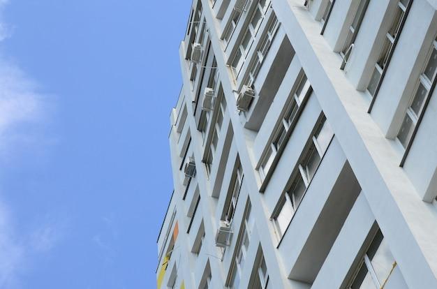 Nowy piętrowy budynek mieszkalny i błękitne niebo