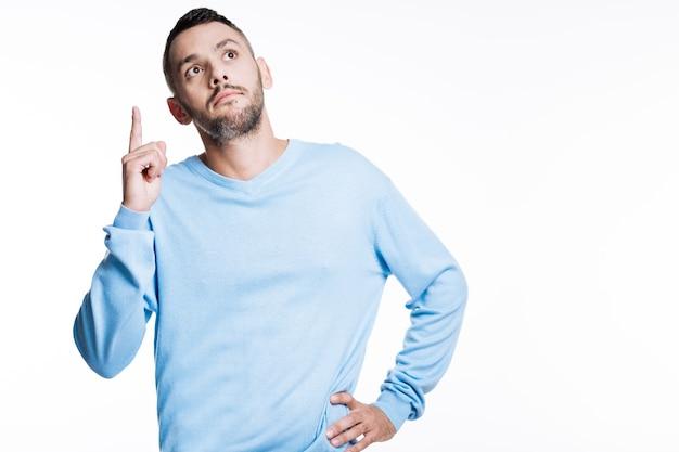 Nowy plan. przystojny ciemnowłosy młody człowiek w niebieskim swetrze, podnosząc palec i patrząc w górę, jakby miał nowy pomysł