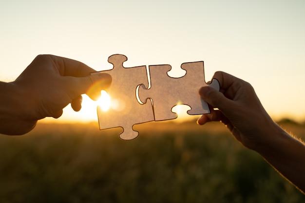 Nowy pomysł i systemowe kobiece dłonie układają puzzle na tle zachodu słońca