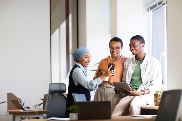 Nowy pracownik płci męskiej rozmawiający z koleżankami w swojej nowej pracy biurowej