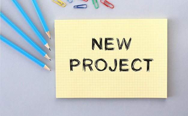 Nowy projekt tekst w notatniku na szarym tle obok ołówków i spinaczy