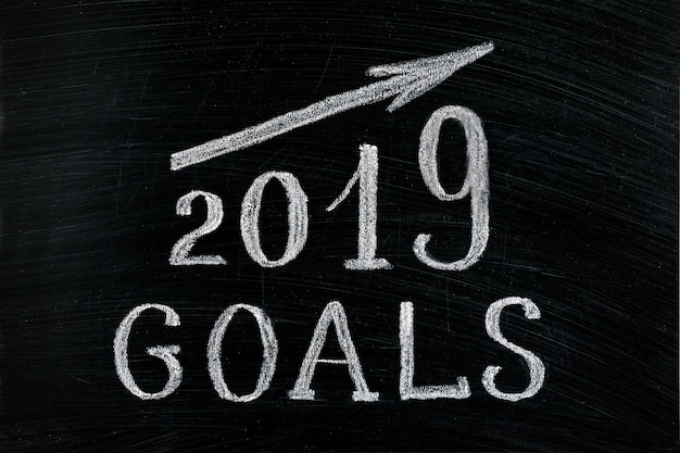 Nowy rok 2019 cele z powstającą strzałkowatą tekst kredą na blackboard