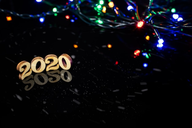 Nowy rok 2020 jasne światła na ciemnym tle i wolne miejsce na tekst.