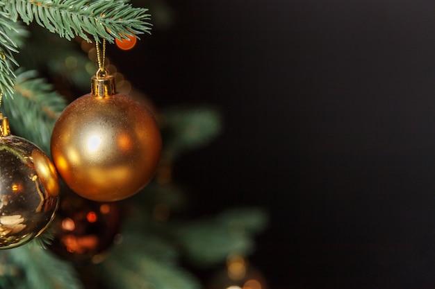 Nowy rok 2020. wesołych świąt wesołych świąt. klasyczne boże narodzenie ozdobione choinką ze złotym ornamentem ozdoby zabawki i piłkę. nowoczesny ciemny czarny apartament w stylu klasycznym