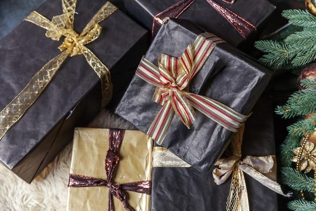 Nowy rok 2020. wesołych świąt wesołych świąt. klasyczne boże narodzenie udekorowane nowy rok drzewo ze złotymi czarnymi pudełkami ozdoby ozdoby. nowoczesny apartament w ciemnym stylu klasycznym
