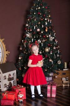 Nowy rok 2020. wesołych świąt, wesołych świąt. mała dziewczynka z świeczką przed choinką i prezentami. wystrój nowego roku, świąteczne wnętrze domu. portret dziecka bożego narodzenia. ferie
