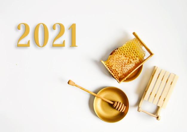 Nowy rok 2021, pęknięty żółty plaster miodu z miodem na stole obok ozdobnych sań
