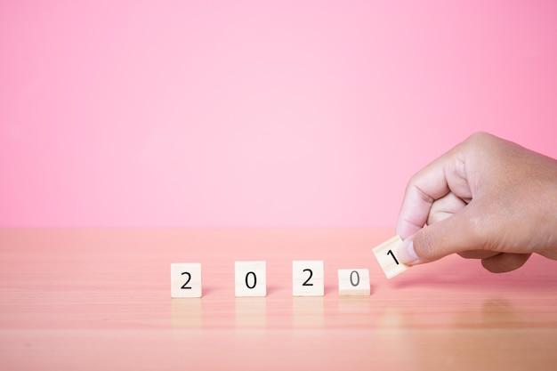Nowy rok 2021 z drewnianą kostką na różowym tle.