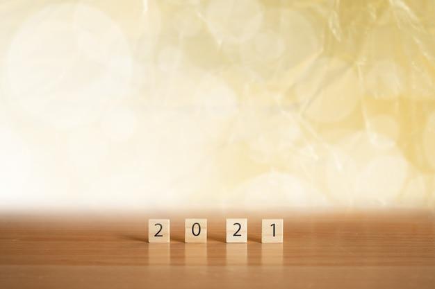 Nowy rok 2021 z drewnianą kostką na złotym tle.