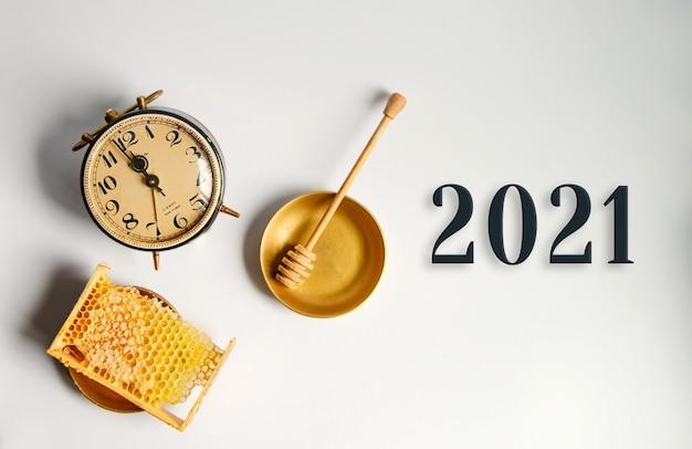 Nowy rok 2021, złamany żółty plaster miodu z miodem w pobliżu budzika