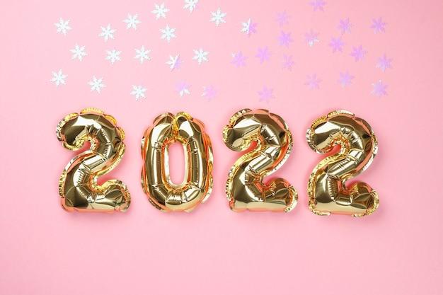 Nowy rok 2022. balony foliowe numery 2022 na różowym tle.