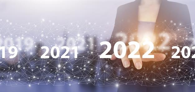 Nowy rok 2022, cel, plan, działanie. ręka dotykowy ekran cyfrowy hologram 2022 znak na światło miasta niewyraźne tło. sukces koncepcji nowego roku. zarządzanie biznesem, pomysły koncepcje inspiracji.