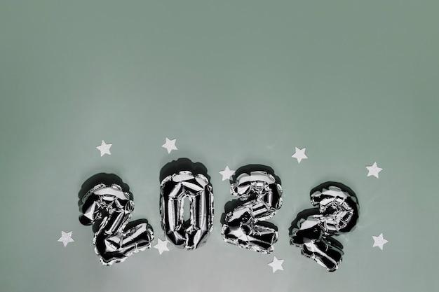 Nowy rok 2022 lub boże narodzenie zielone tło płaskie leżał. widok z góry na 2022 balonowe srebrne lub metalowe liczby z białymi gwiazdami. koncepcja zaproszenia lub karty z pozdrowieniami. świąteczny nastrój. zdjęcie wysokiej jakości
