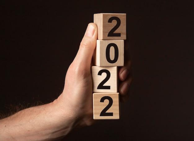 Nowy rok 2022 napis, numery na drewnianych kostkach w męskiej ręce na czarnym tle.