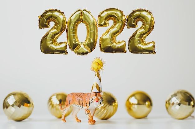 Nowy rok 2022 złote balony foliowe numer 2022 i symbol tygrysa chińskiego nowego roku w czapce imprezowej