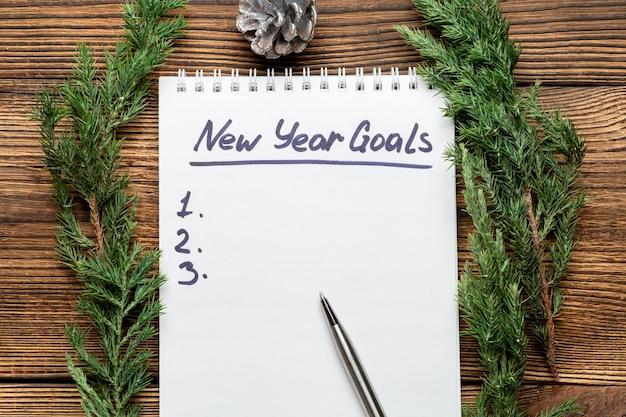 Nowy rok cele napis w notatniku z gałęzi świerkowych i zabawki choinkowe