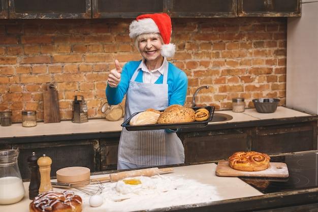 Nowy rok gotowania. portret atrakcyjna starsza starzejąca się kobieta gotuje na kuchni. babcia robi smakowitemu świątecznemu pieczeniu.