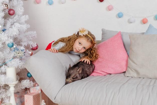 Nowy rok i boże narodzenie. dziewczyna w świątecznej odzieży i mini świni. symbol świni 2019. czarna świnia. horoskop chiński. przyjaźń i troska o młodszych