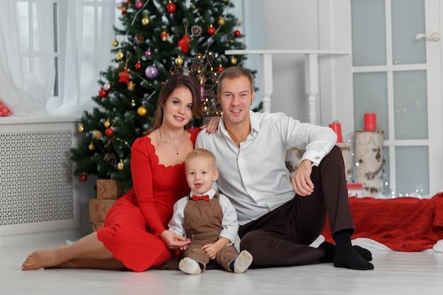 Nowy rok i boże narodzenie portret młodej rodziny w klasycznych ubraniach. szczęśliwego nowego roku i koncepcji bożego narodzenia