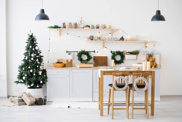 Nowy rok i boże narodzenie. świąteczna kuchnia skandynawska w świątecznych dekoracjach. świece, gałęzie jodły, stojaki drewniane, stół.