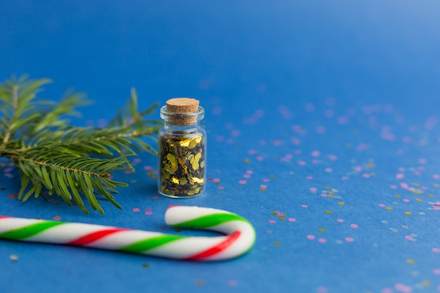 Nowy rok i boże narodzenie wakacje niebieskie tło. koncepcja wakacji, zakupów i sprzedaży. mała szklana butelka z konfetti, cukierkami i sosnowymi gałązkami.