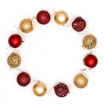 Nowy rok i ramki świąteczne. czerwone i złote ozdoby świąteczne - błyszczące kulki i ozdobna wstążka na białym tle papieru. nowy rok, koncepcja bożego narodzenia. widok z góry, płaski układ, miejsce na kopię