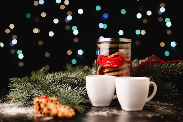 Nowy rok i świąteczny wystrój. butelka z czekoladowymi ciasteczkami i filiżankami do herbaty