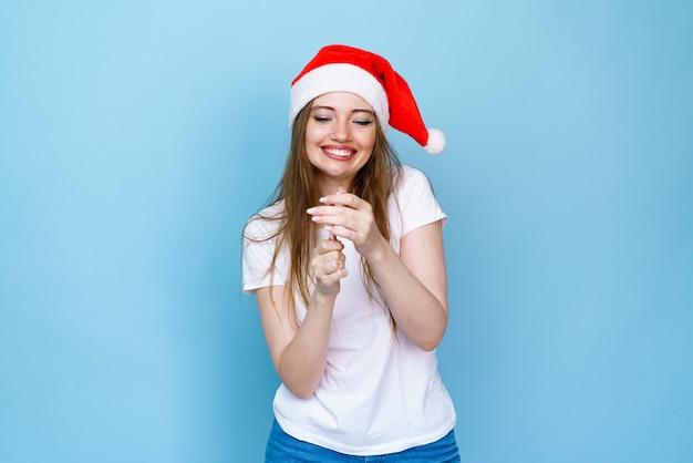 Nowy rok i święta bożego narodzenia koncepcja uśmiechnięta młoda kobieta w czapce świętego mikołaja z lizakiem na niebiesko...