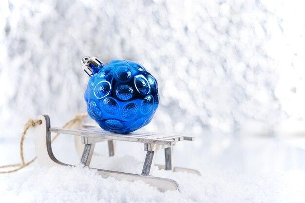 Nowy rok, kartkę z życzeniami świątecznymi. małe ozdobne drewniane sanki do zabawy na śniegu z jasnoniebieską kulką choinkową. bokeh. boże narodzenie tło.