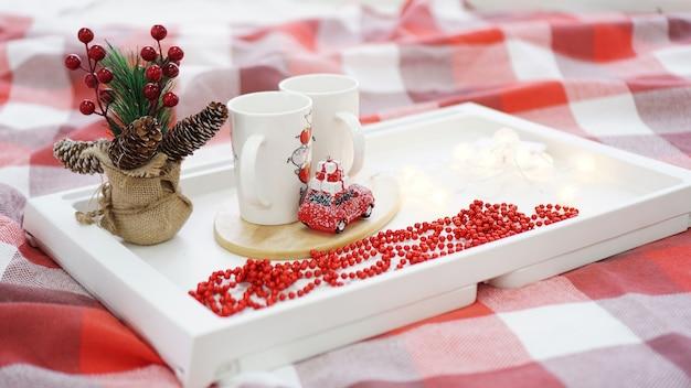 Nowy rok lub świąteczny czerwony kubek na białej tacy w czerwono-białym łóżku ze światłami