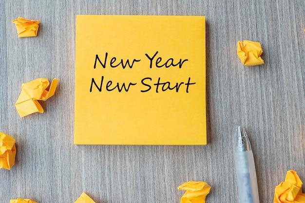 Nowy rok nowy start słowo na żółtej notatce