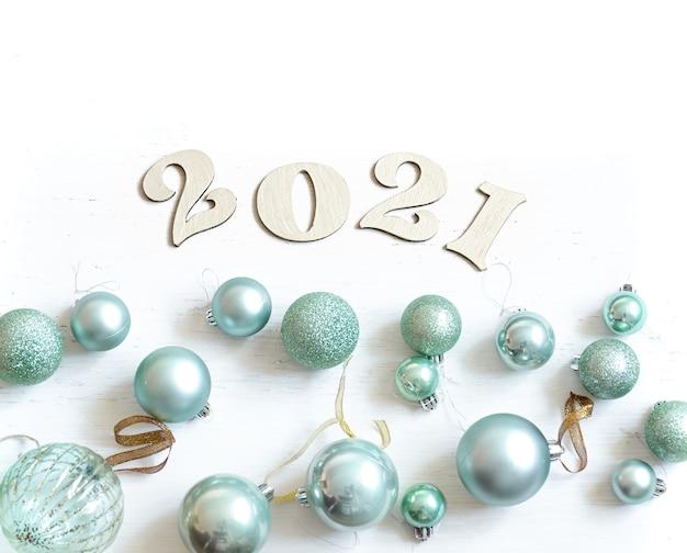 Nowy rok skład z drewnianym numerem na nadchodzący rok i niebieskie bombki na białym tle.