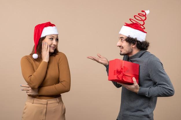 Nowy rok świąteczna koncepcja nastroju z uroczą parą w czerwonych czapkach świętego mikołaja dziewczyna podarowała mu prezent na szaro