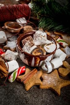 Nowy rok, świąteczne przysmaki, słodycze. kubek gorącej czekolady ze smażonym ptasie mleczko, ciasteczka z imbirową gwiazdą, piernikowi mężczyźni, cukierki w paski, przyprawy anyż cynamonowy, kakao, cukier puder. widok z góry