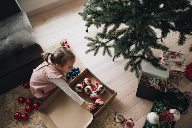 Nowy rok. udekoruj choinkę. sztuczne drzewo. dziewczyna w różowej sukience z kucykami zdobi choinkę. świąteczne zabawki w pudełku. w oczekiwaniu na wakacje.