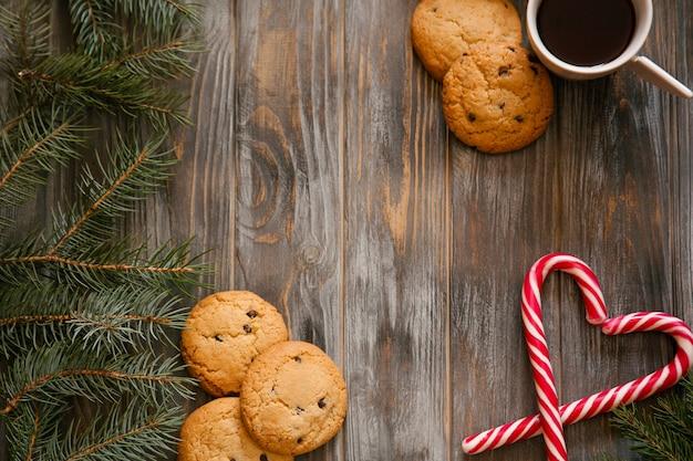 Nowy rok wakacje wystrój na drewnianym tle. filiżanka kawy ciasteczka czekoladowe i trzciny cukrowej w kształcie serca. przytulna koncepcja zimowego nastroju. gałąź jodły po lewej stronie.