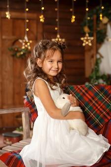 Nowy rok . wesołych świąt, wesołych świąt. mała dziewczynka w białej sukni siedzi na ławce z białym królikiem. magic light in night xmas tree interior