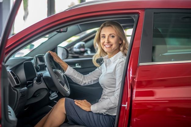 Nowy samochód. blondynka ładna kobieta siedzi w czerwonym samochodzie