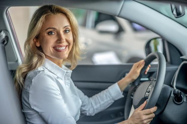 Nowy samochód. blondynka ładna kobieta siedzi w nowym samochodzie i uśmiecha się