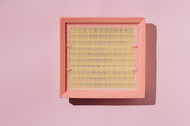Nowy samochodowy filtr powietrza na różowym tle