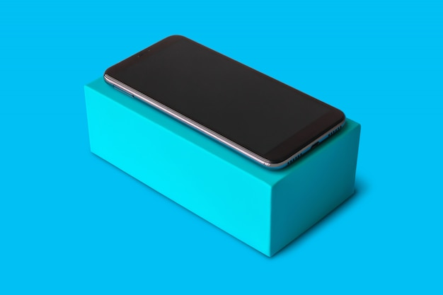 Nowy smartfon na niebieskim tle do makiety