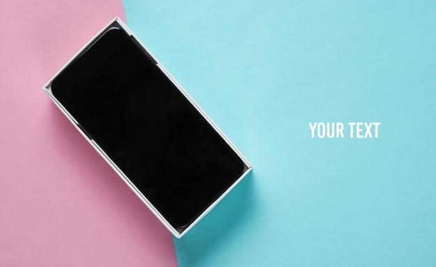 Nowy smartfon w otwartym pudełku na kolorowym tle papieru. widok z góry, minimalizm. skopiuj miejsce