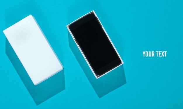Nowy smartfon w otwartym pudełku na niebieskim tle papieru. widok z góry, minimalizm. skopiuj miejsce