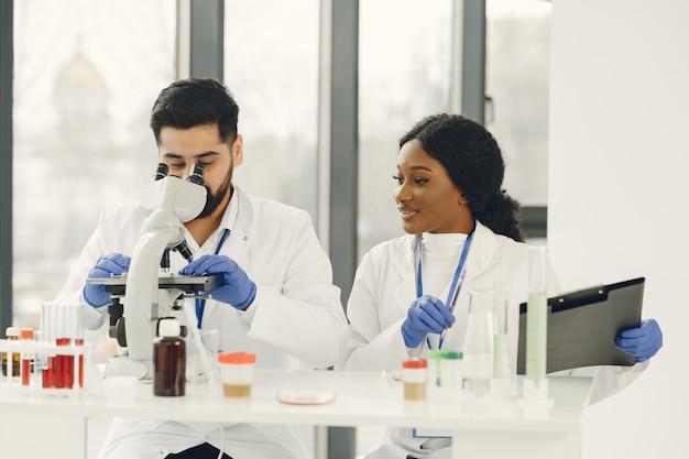 Nowy test. skoncentrowani wykwalifikowani badacze w mundurach. robię testy, tworzymy szczepionkę.