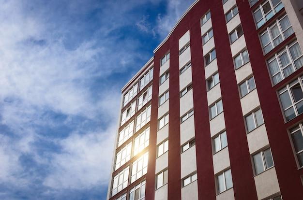 Nowy wielokondygnacyjny budynek na tle nieba, w którego oknach odbija się słońce