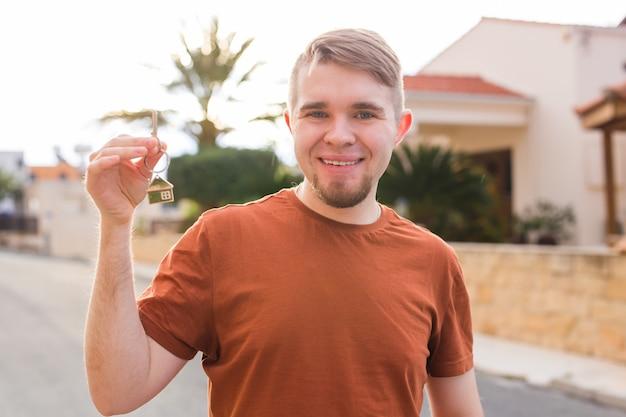 Nowy właściciel mieszkania w domu i koncepcja ludzi z bliska z kluczami, które pokazują młodego szczęśliwego mężczyznę z nowym .