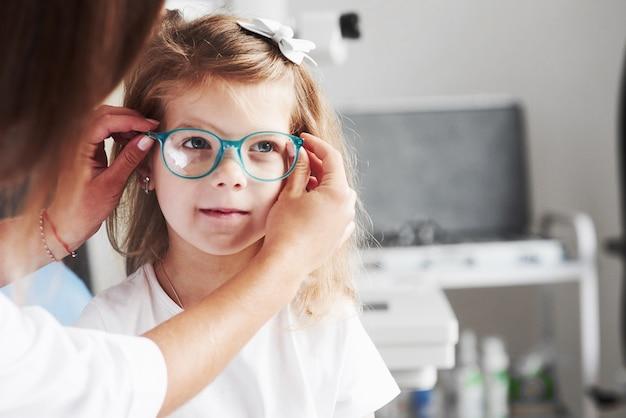 Nowy wygląd. lekarz daje dziecku nowe okulary do jej widzenia.