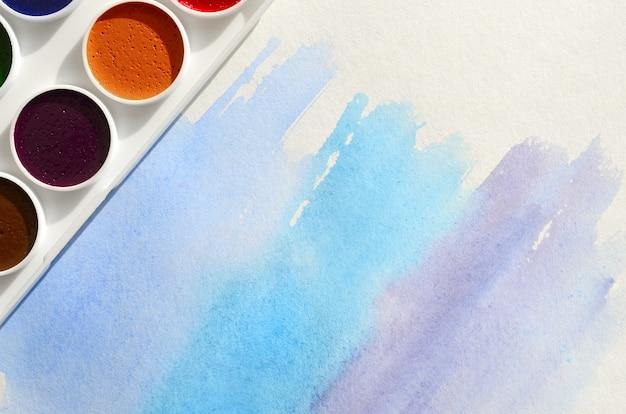 Nowy zestaw akwareli leży na kartce papieru, która pokazuje abstrakcyjny rysunek akwarelowy w postaci niebieskich kresek.
