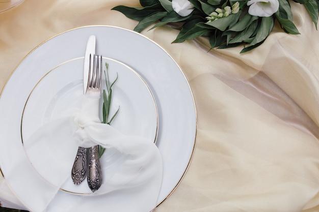 Nóż, biały talerz i widelec na beżowym obrusie
