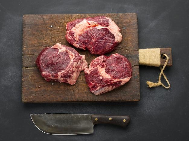 Nóż i surowy kawałek wołowiny ribeye na czarnym stole, widok z góry